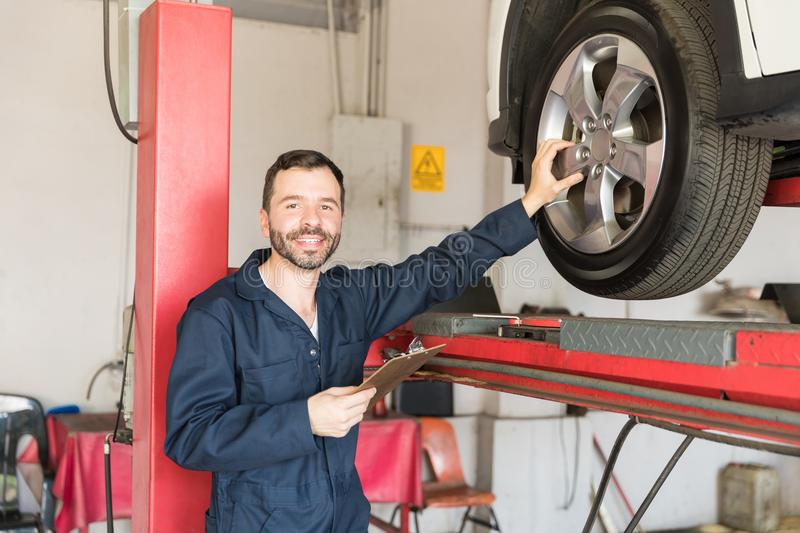 Serviceman Analyzing Tire While Holding Clipboard In Workshop royalty free stock photos