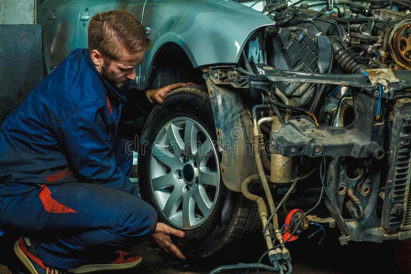 Serviceman checking suspension in a car at garage. Mechanic repaired wheeled vehicles. Mechanic Holding Car Tire At Garage. Mechan. Ician changing car wheel in stock images