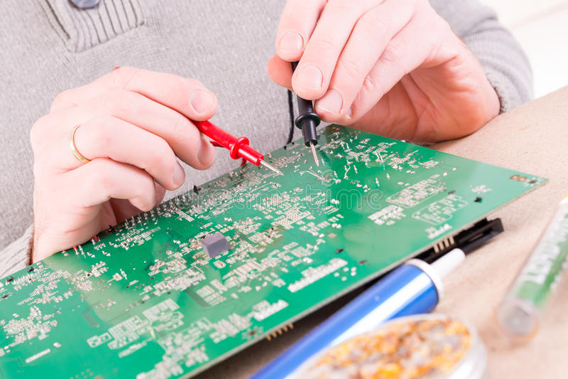 Serviceman checks PCB with a digital multimeter. In the service workshop stock photography