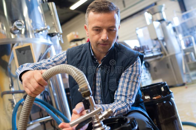 Serviceman operating industrial water purification or filtration equipment royalty free stock photography