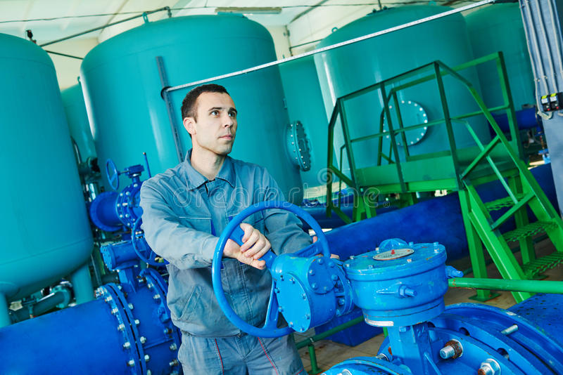 Serviceman operating industrial water purification or filtration equipment royalty free stock photo