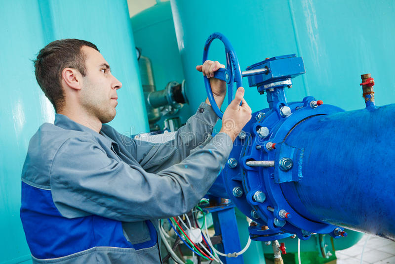 Serviceman operating industrial water purification or filtration equipment. Worker serviceman operating industrial water purification filtration equipment in royalty free stock photos