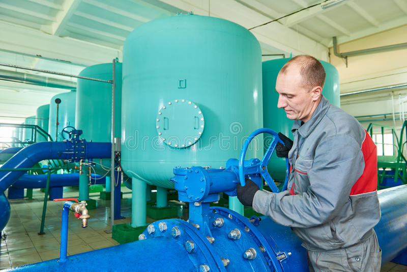 Serviceman operating industrial water purification or filtration equipment royalty free stock image