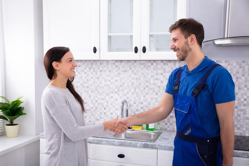 Serviceman Shaking Hands With Woman. Smiling Young Male Serviceman Shaking Hands With Happy Woman royalty free stock images