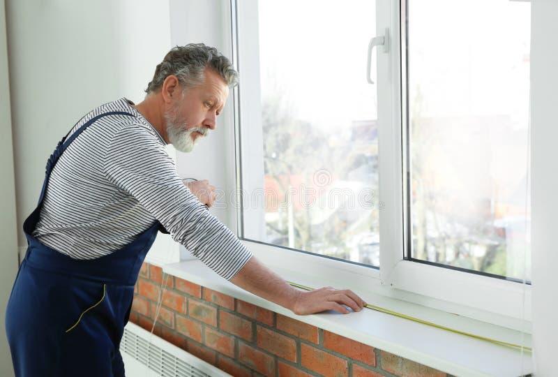 Serviceman som mäter fönstret för installation royaltyfri fotografi