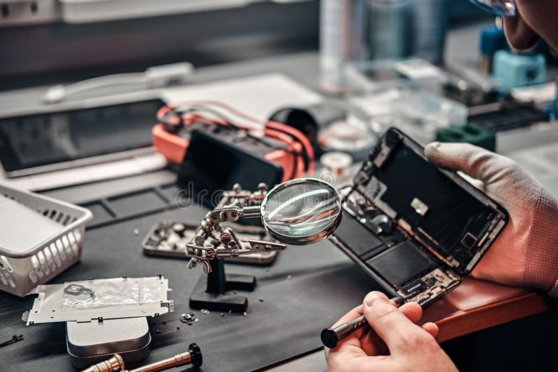 Serviceman uses magnifier and screwdriver to repair damaged smartphone in the workshop. royalty free stock photography