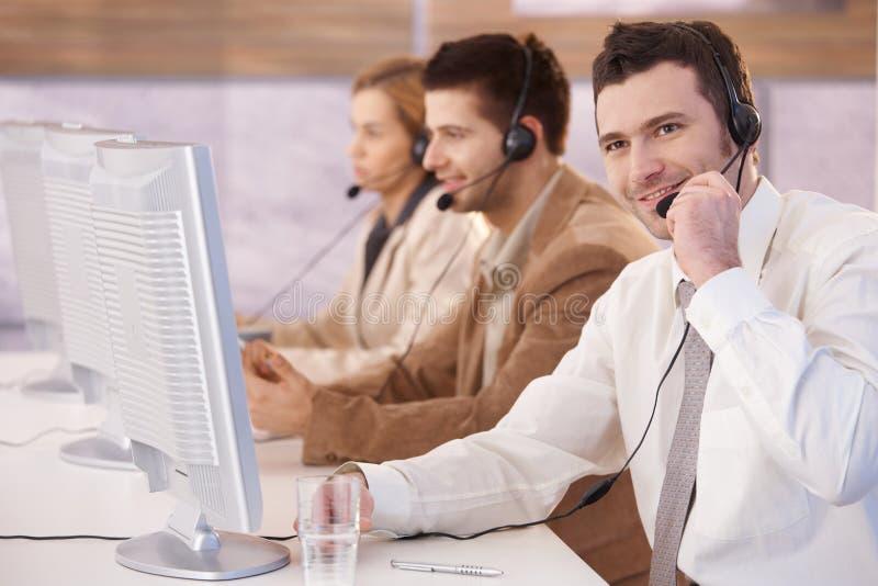 Servicer alegre do cliente que trabalha no centro de chamadas fotografia de stock