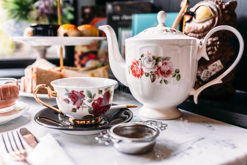 Services à thé anglais de roses de porcelaine de cru comprenant la théière, la tasse de thé, le plat, la cuillère et le filtre de photographie stock
