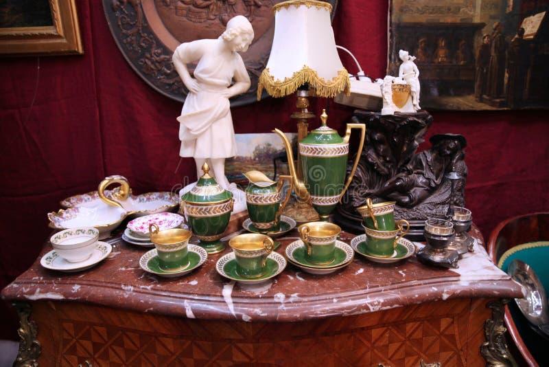 Services à thé de porcelaine de cru et articles intérieurs sur un vieux coffre des tiroirs image stock