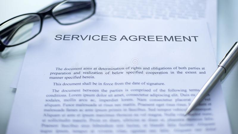 Services agreement lying on table, pen and eyeglasses on official document. Stock photo stock photo