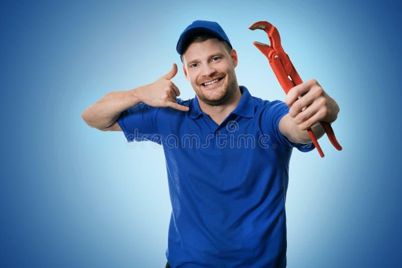 Services de tuyauterie - plombier avec la clé montrant le geste d'appel téléphonique photo stock
