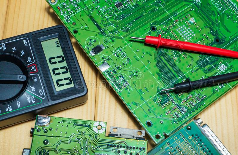 Services for the production of electronics and repair on a wooden background. Electronic board components and tester stock images