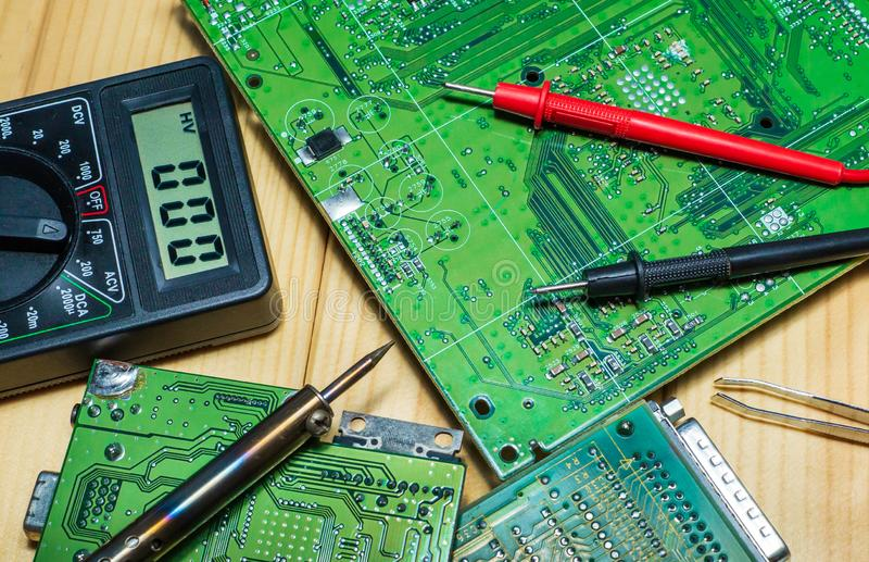 Services for the production of electronics and repair on a wooden background. Electronic board components and tester royalty free stock image