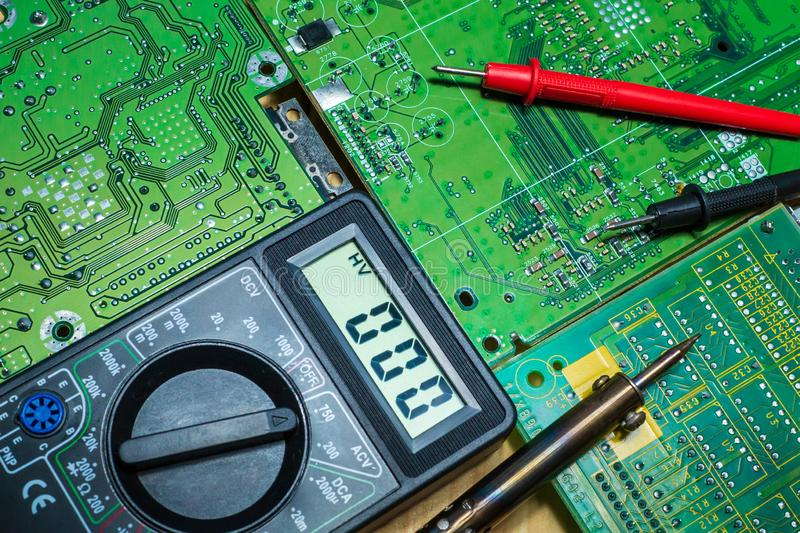 Services for the production of electronics and repair on a wooden background. Electronic board components and tester stock photos