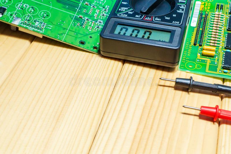 Services for the production of electronics and repair on a wooden background. Electronic board design and tester stock images