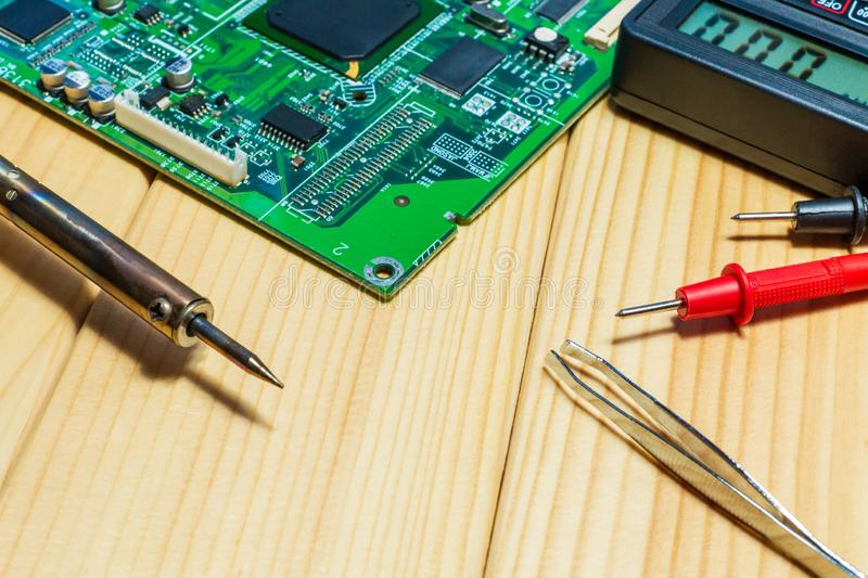 Services for the production of electronics and repair on a wooden background. A set of tools and electronic boards royalty free stock photo