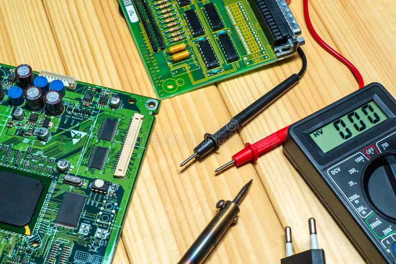Services for the production of electronics and repair on a wooden background. A set of tools and electronic boards stock images