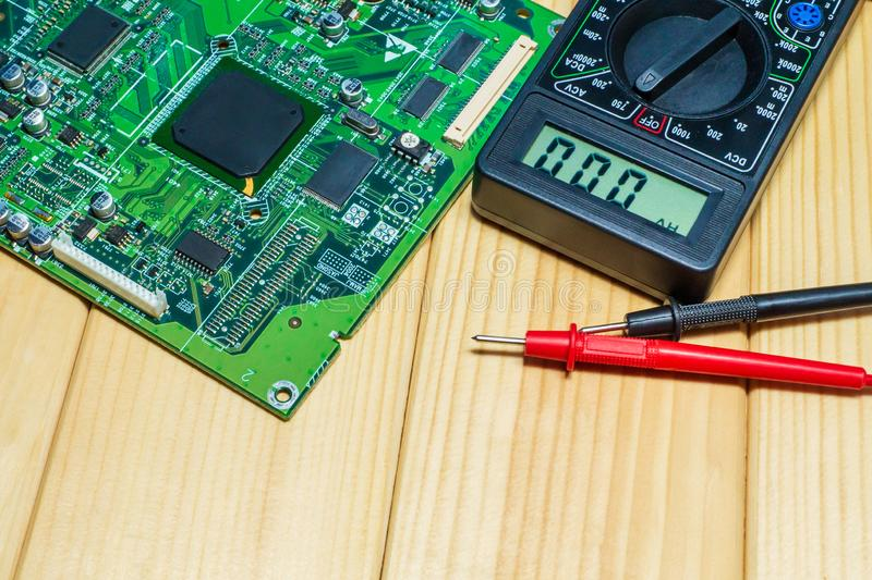 Services for the production of electronics and repair on a wooden background. A set of tools and electronic boards stock photo