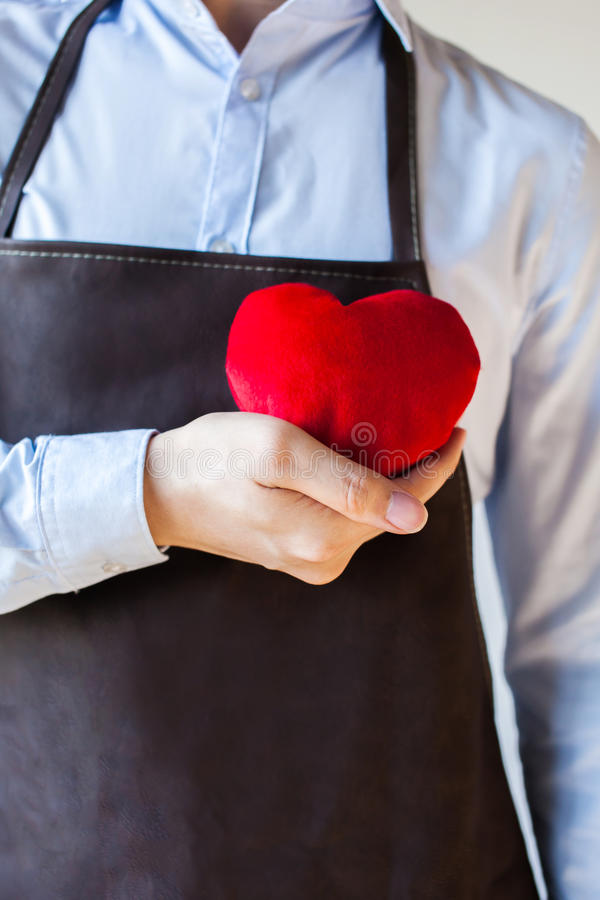 Servicing man in apron holding heart - customer relationship and service minded business concept stock images