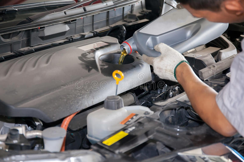 Servicing mechanic pouring new oil lubricant into the car engine.  royalty free stock photo