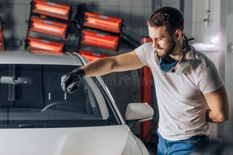 Servicio de atención al cliente hombre que trabaja con un inspector de la pintura para probar la profundidad de la pintura fotos de archivo