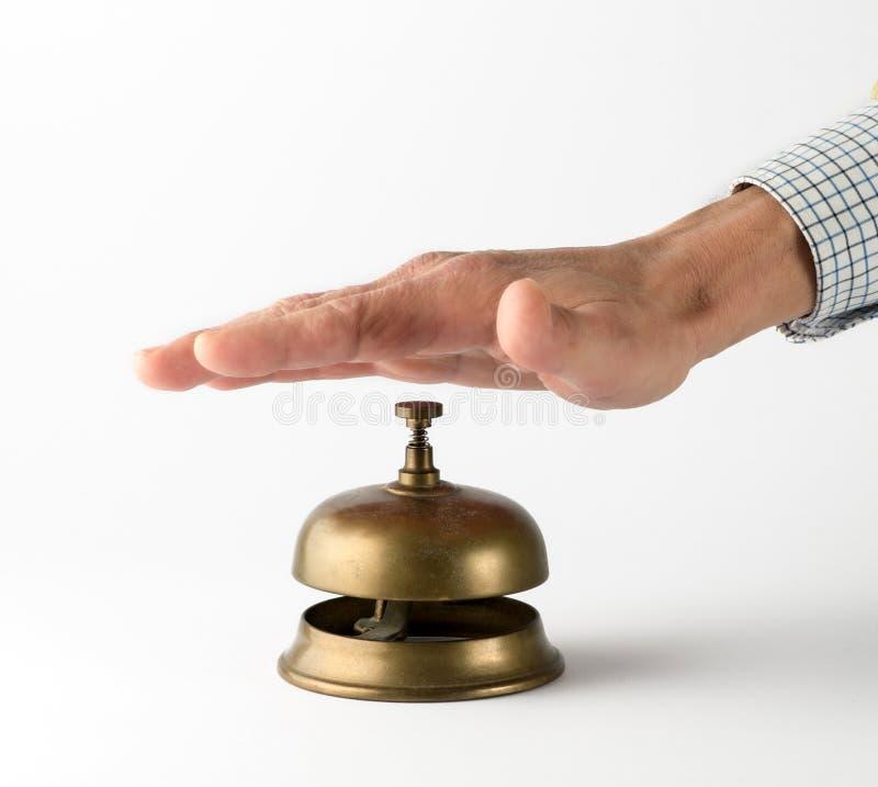 Servicio de cobre amarillo de sonido Bell de la mano masculina fotografía de archivo