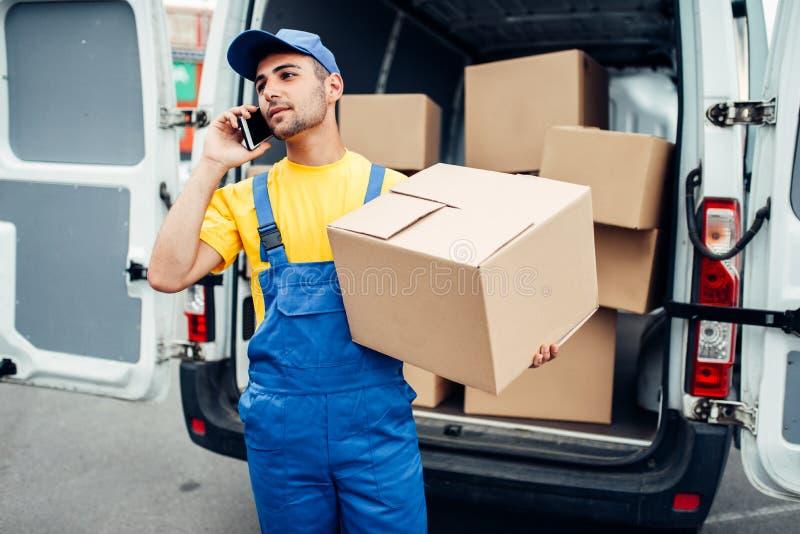 Servicio de entrega del cargo, mensajero con la caja y teléfono imagen de archivo