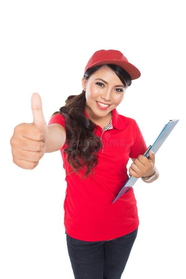 Servicio de entrega femenino feliz con el tablero que muestra el pulgar para arriba imágenes de archivo libres de regalías