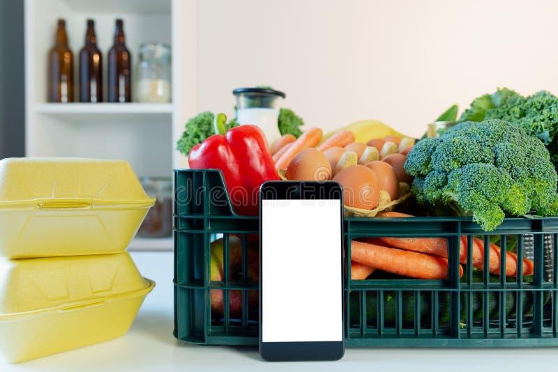 Servicio de entrega de la comida - smartphone delante de la caja de ultramarinos fotos de archivo