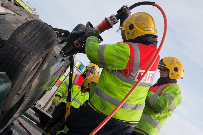 Servicio de fuego y de rescate en el entrenamiento del choque de coche imagenes de archivo