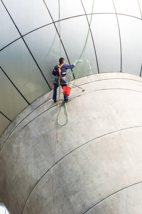 Servicio de las ventanas de la limpieza en el alto edificio de la subida es peligroso fotografía de archivo libre de regalías