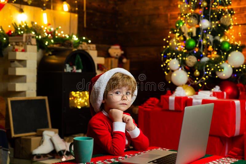Servicio de los regalos Peque?o ayudante de Pap? Noel Internet que practica surf del ni?o elegante Sombrero y traje de santa del  fotografía de archivo