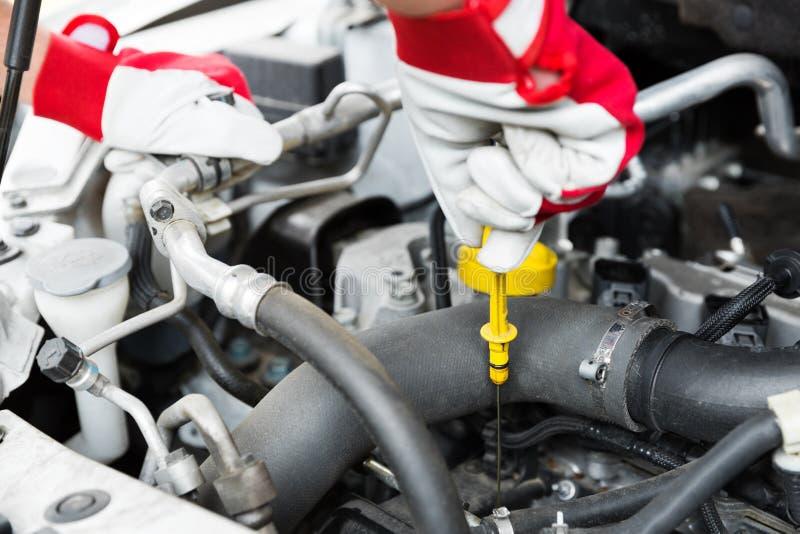 Servicio de mantenimiento del coche - nivel de aceite de motor del control del mecánico imagen de archivo