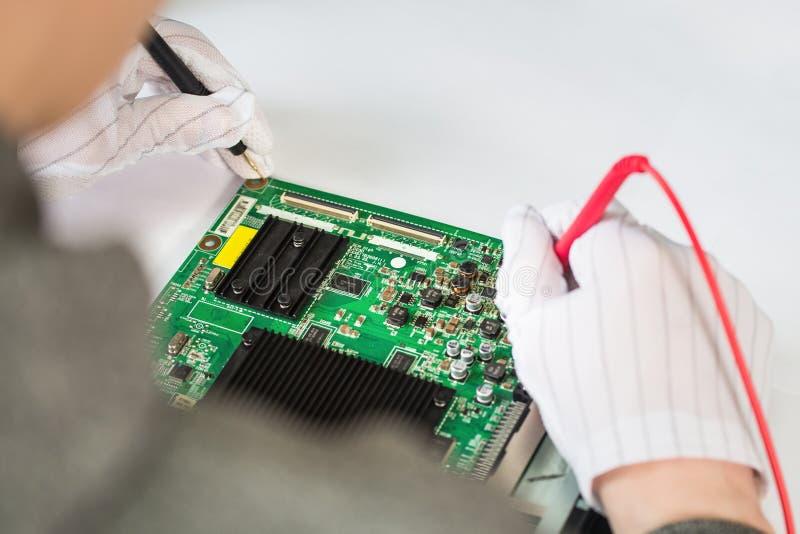 Servicio de reparación del ordenador, manos de la placa madre de la prueba de la tecnología del hombre con las herramientas imagen de archivo