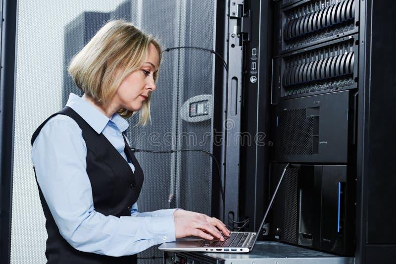 Servicio del almacenamiento de la nube el ingeniero de sexo femenino trabaja con el ordenador portátil en centro de datos foto de archivo