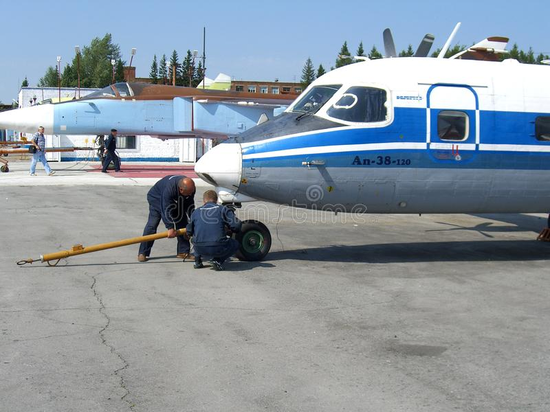 Servicio del Antonov ruso an-38 en los trabajadores del técnico del campo de aviación imagenes de archivo