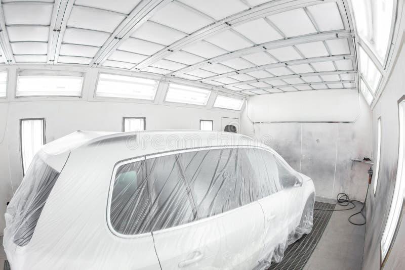Servicio del coche de la pintura del garaje el veh?culo se cubre con el papel protector Reparando el trabajo de carrocería despué fotografía de archivo libre de regalías