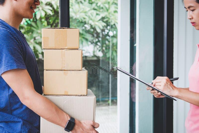 Servicio del servicio a domicilio y trabajo con la mente del servicio, cliente de la mujer que firma y que recibe un paquete de l imagen de archivo