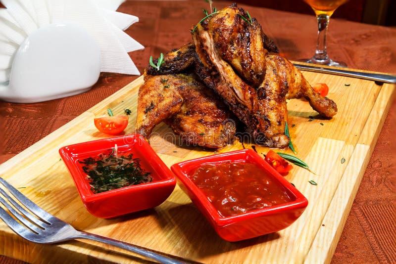 Servicio del pollo del restaurante en un tablero de madera con las salsas fotos de archivo libres de regalías