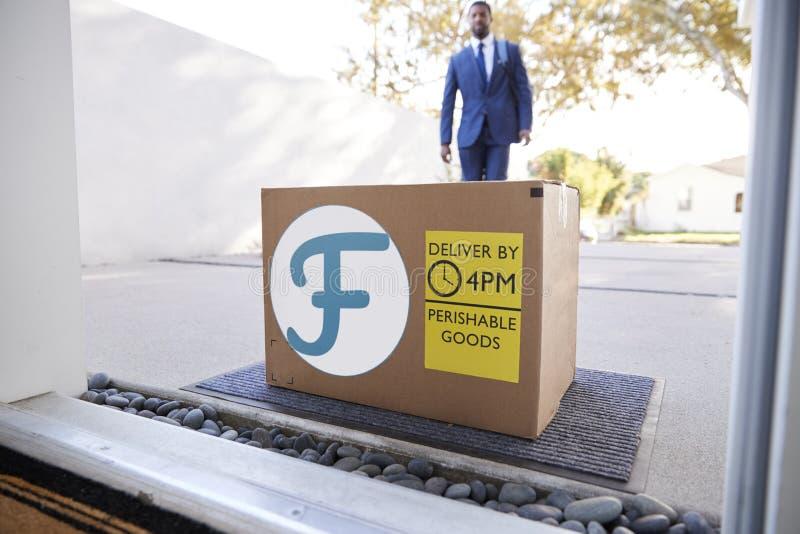 Servicio a domicilio de la comida fresca de Coming Home To del hombre de negocios en caja de cartón fuera de Front Door foto de archivo