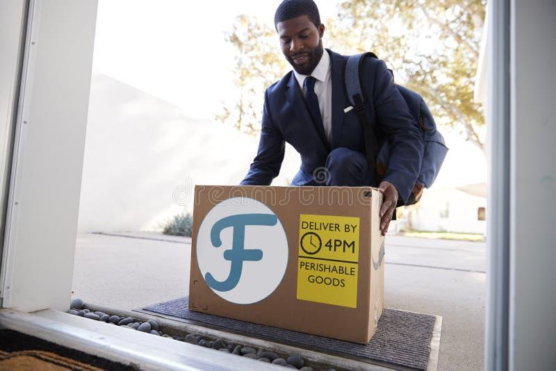 Servicio a domicilio de la comida fresca de Coming Home To del hombre de negocios en caja de cart?n fuera de Front Door fotos de archivo libres de regalías