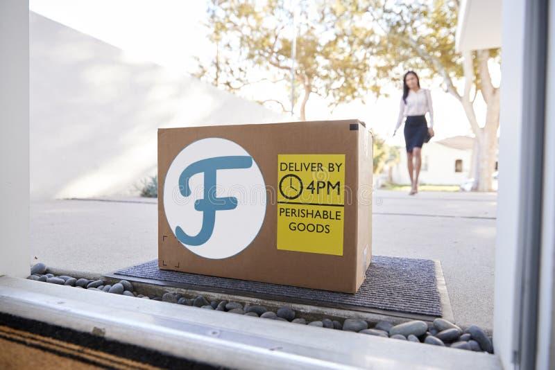 Servicio a domicilio de la comida fresca de Coming Home To de la empresaria en caja de cart?n fuera de Front Door imágenes de archivo libres de regalías