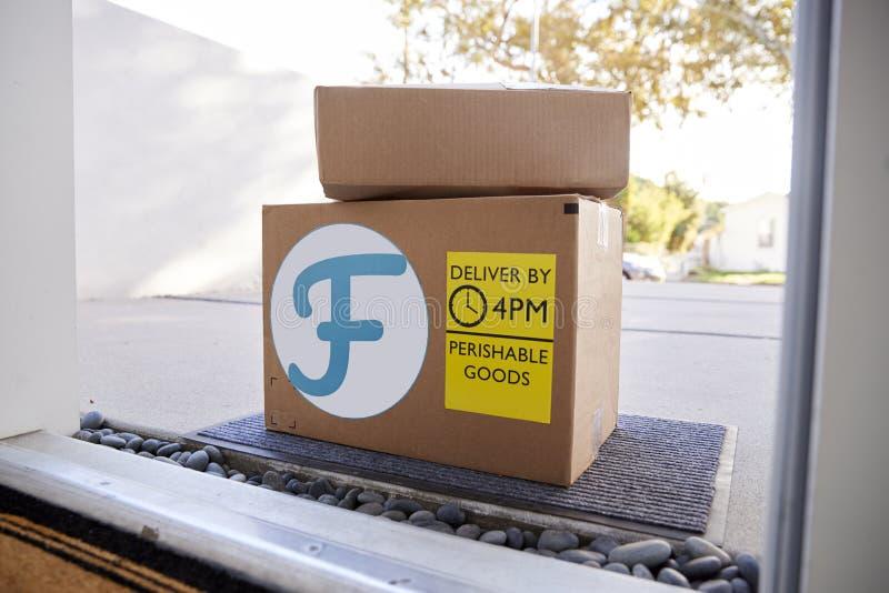 Servicio a domicilio de la comida fresca en cajas de cartón fuera de Front Door imagen de archivo
