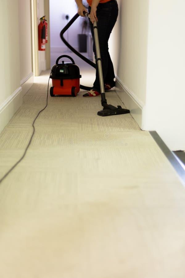 Servicio profesional de la limpieza Alfombra hoovering de la mujer en oficina fotos de archivo