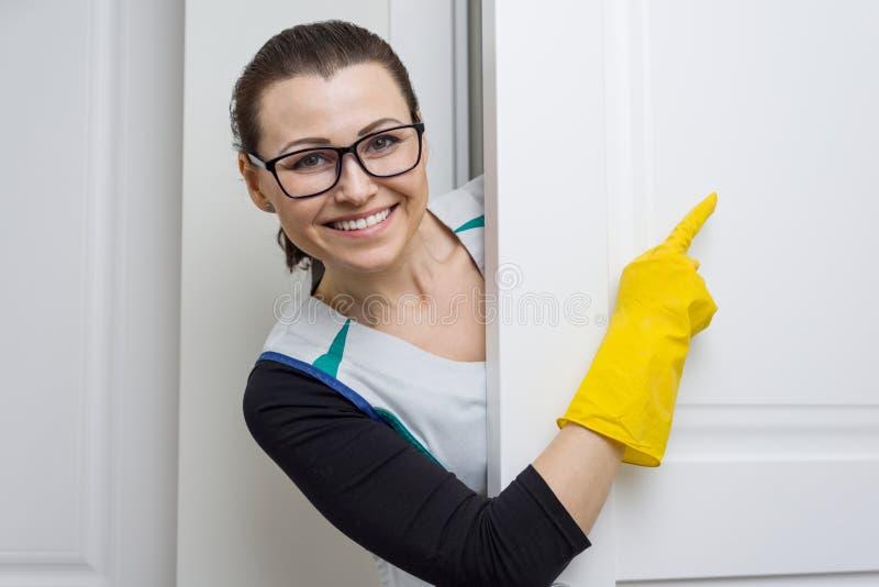 Servicio profesional de la limpieza La criada de la mujer en guantes de goma amarillos que señala con un finger a la puerta blanc foto de archivo libre de regalías