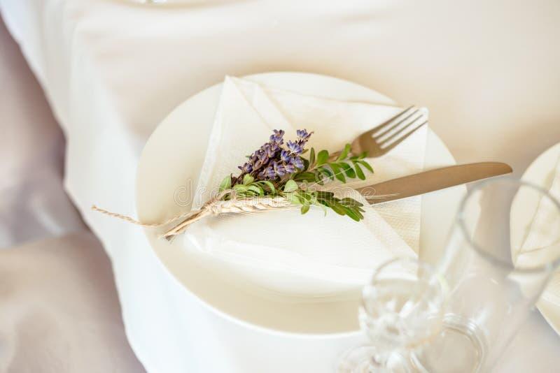 Servido con las flores y la placa blanca dinning de la tabla del lavander foto de archivo libre de regalías