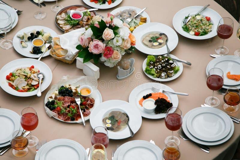 Servido para a tabela do restaurante do banquete com vidros dos pratos, do petisco, da cutelaria, do vinho e de água, alimento eu fotografia de stock royalty free