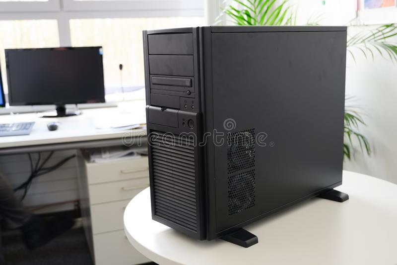 Servidor negro en una caja de la torre en una tabla blanca en la oficina, foco seleccionado foto de archivo libre de regalías