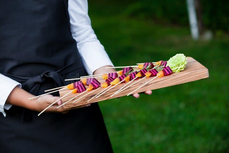 Servidor que guarda uma bandeja de madeira completamente de petiscos durante um evento abastecido imagem de stock royalty free