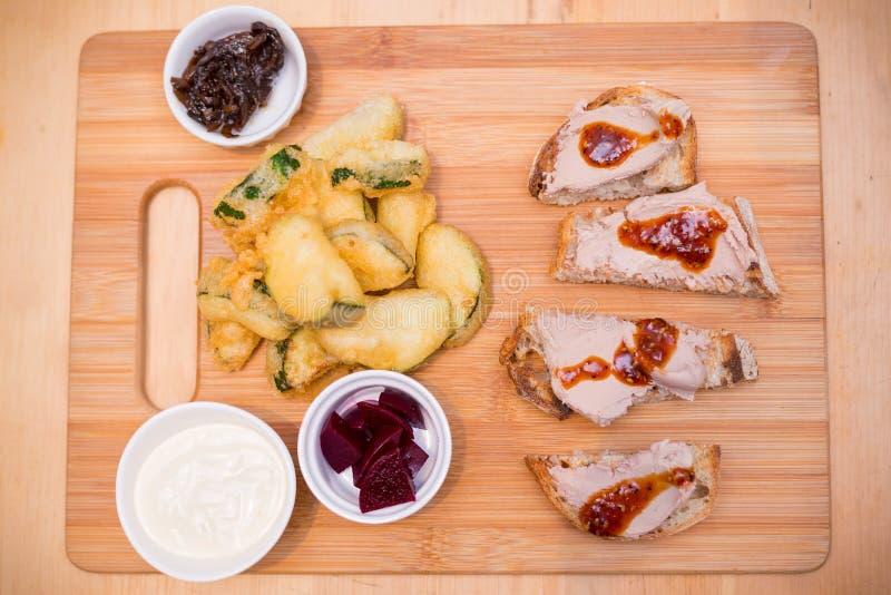 Servierplatte mit frittiertem Zucchini- und hühnerleber crostini lizenzfreie stockfotografie